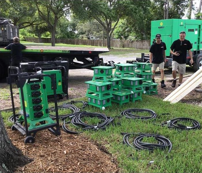 SERVPRO techs and SERVPRO restoration equipment stacked outside