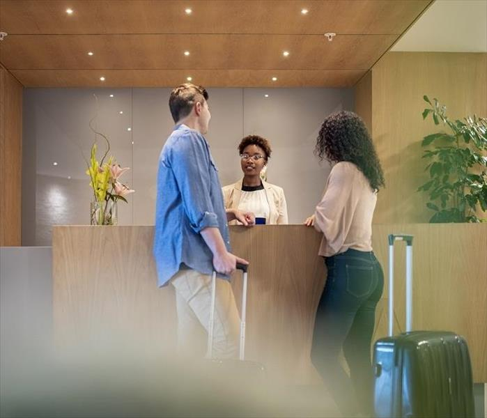 Man, woman and clerk at front desk of motel
