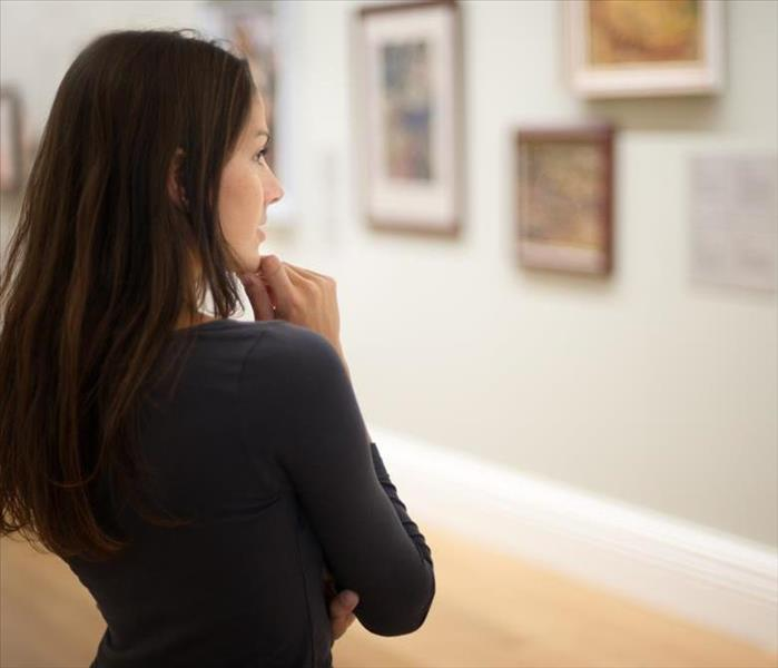 A woman looking at a wall with paintings.